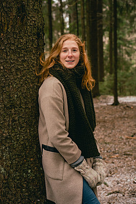 Portrait confident redhead woman in scarf and wool coat leaning against tree in woods - p301m2202370 by Vasily Pindyurin