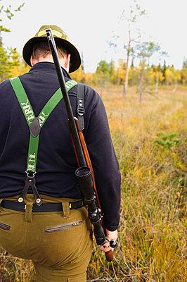 Hunter walking in forest with gun - p31225179 by Hans Berggren