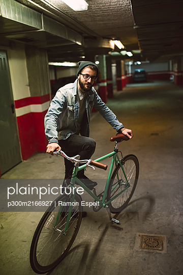 Young man standing in park house with his fixie bike - p300m2166927 by Ramon Espelt