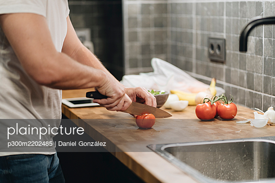 Mature man standing in kitchen, slicing tomatoes - p300m2202485 by Daniel González