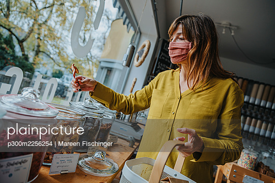 Mature female customer in mask picking up food while shopping in zero waste store during pandemic - p300m2256254 by Mareen Fischinger