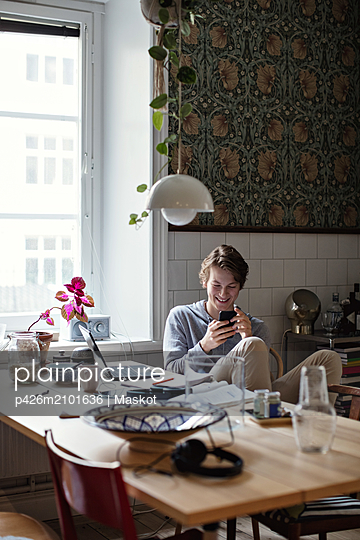 Smiling teenage boy using social media on mobile phone while studying at home - p426m2101636 by Maskot