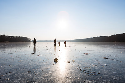 Germany, Brandenburg, Lake Straussee, frozen lake and silhouettes of people walking on ice - p300m1580923 by Julia Otto