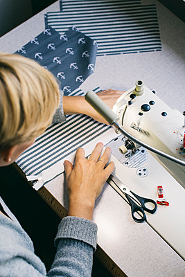 Woman using sewing machine on table in studio - p300m2029792 by Visualspectrum