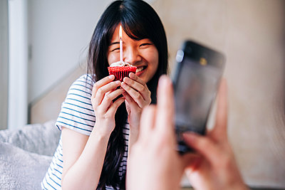 Woman taking photo of smiling friend with cupcake through mobile phone at home - p300m2293302 by Angel Santana Garcia