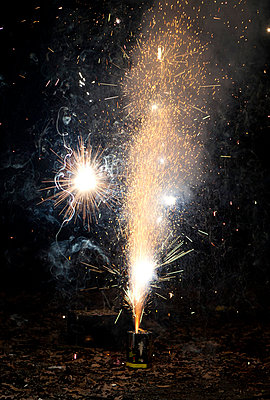 Sparks and smoke coming out of a firework exploding on a sidewalk - p301m799652f by Halfdark