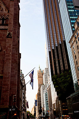 Low angle view of skyscrapers and American flags hanging, New York - p312m798684 by Pia Ulin
