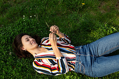 Young woman on a meadow with a blade of grass - p341m2210433 by Mikesch