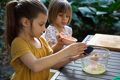 Two young sisters pouring lemon juice for lemonade at garden table - p924m1446959 by Kinzie Riehm