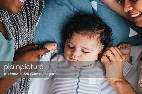 Overhead view of cute baby boy sleeping with lesbian mothers on bed at home - p1166m2130580 by Cavan Images