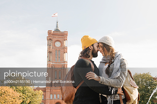 Young couple embracing with Rotes Rathaus in background, Berlin, Germany - p300m2155190 by Hernandez and Sorokina