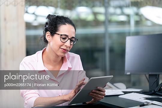 Female entrepreneur using digital tablet while sitting at desk in office - p300m2265174 by Florian Küttler