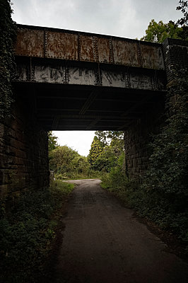 Railway bridge over deserted rural lane - p1047m1475147 by Sally Mundy