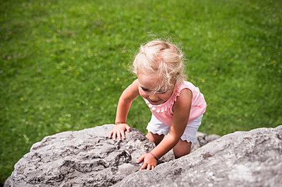 Kleines Mädchen klettert auf Stein - p1142m2107599 von Runar Lind