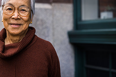 Portrait of smiling senior woman wearing glasses in the city - p1166m2285618 by Cavan Images
