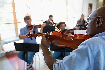 High school teacher with violin leading lesson - p1192m1085916f by Hero Images