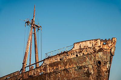 Detailaufnahme vom Bug und Mast eines rostigen Schiffswracks gegen den blauen Himmel - p1400m1475087 von Bastian Fischer