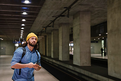 Portrait of man with smartphone waiting at platform, Berlin, Germany - p300m2143417 by Hernandez and Sorokina