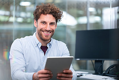 Smiling male entrepreneur holding digital tablet at office - p300m2266005 by Florian Küttler