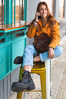 Smiling woman talking on mobile phone while sitting on stool at sidewalk cafe - p300m2266409 by Josu Acosta