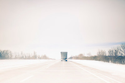 Truck driving on snowy rural road - p429m664769 by Hugh Whitaker