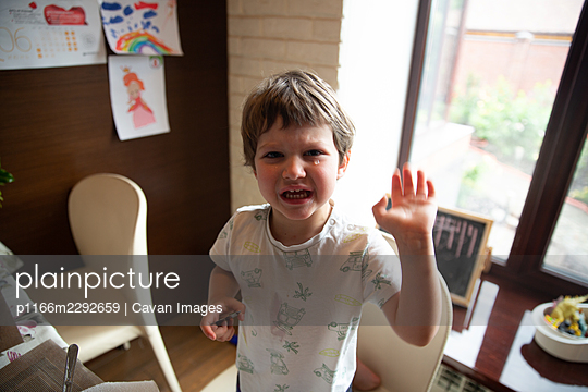 young boy cries at the table - p1166m2292659 by Cavan Images