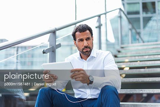 Businessman using tablet, earphone - p300m1587481 von Daniel Ingold