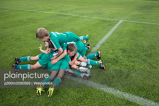 Germany, young football players lying on top of each other - p300m2090569 by Westend61