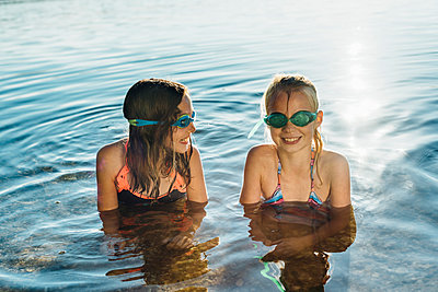 Two smiling friends with swimming goggles at lakeshore - p300m1499528 by Jana Mänz
