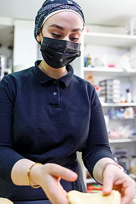 Female baker wearing protective face mask working in bakery - p300m2281925 by Ignacio Ferrándiz Roig