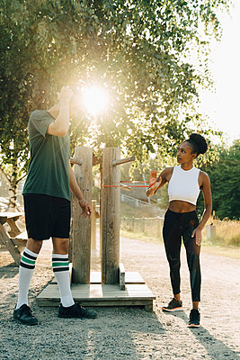 Sportsman and sportswoman exercising with resistance band in park on sunny day - p426m2270806 by Maskot