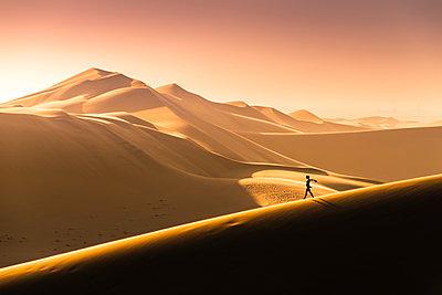Walvis Bay, Namibia, Africa. Tourist walking on the sand dunes at sunset. - p651m2033389 by Marco Bottigelli