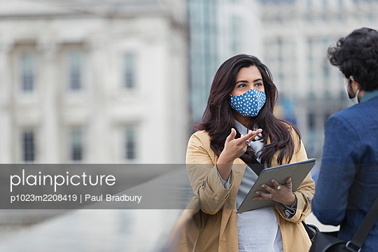 Business people in face masks with digital tablet talking outdoors - p1023m2208419 by Paul Bradbury