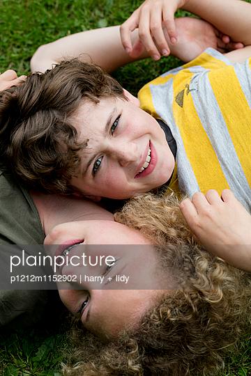 Junge und Mädchen auf dem Rücken im Garten - p1212m1152902 von harry + lidy