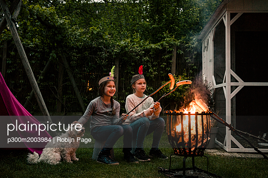 Two girls wearing feather headdress, grilling sausage over camp fire, dog sitting on meadow - p300m2003984 by Robijn Page