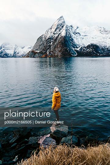 Tourist standing on a rock enjoying the view at Hamnoy, Lofoten, Norway - p300m2166505 von Daniel González