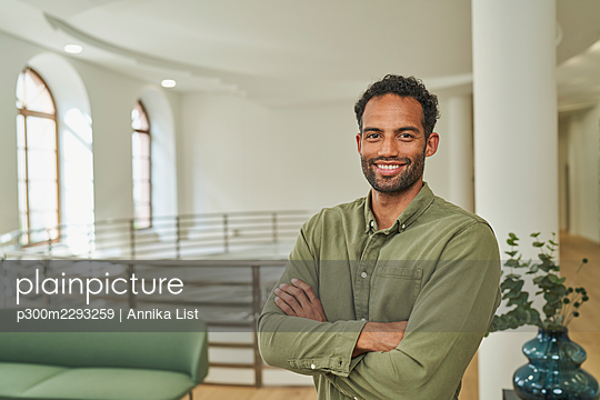 Smiling male professional standing with arms crossed in office - p300m2293259 by Annika List