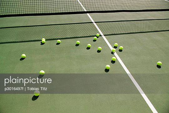 Tennis balls scattered on a tennis court