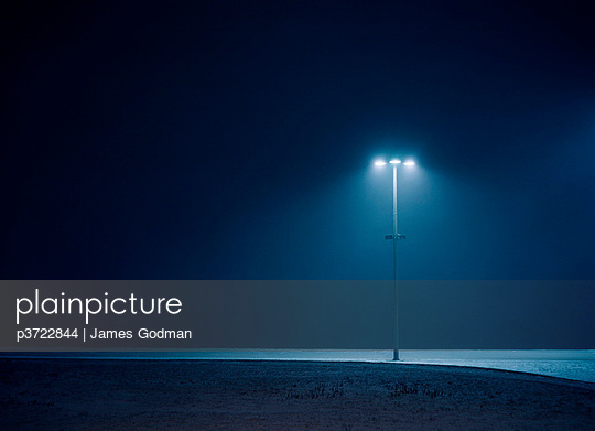 Single lamp post standing in dark landscape - p3722844 by James Godman