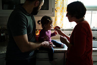 Mother feeding food to daughter sitting by father at kitchen counter - p1166m1509149 by Cavan Images