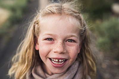 Close-up portrait of happy girl with blond hair standing in forest - p1166m2025054 by Cavan Images