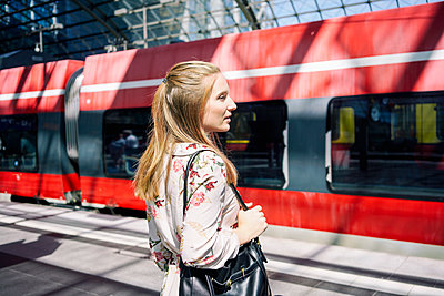 A female waiting for a train in a train station - p1332m2045766 by Tamboly