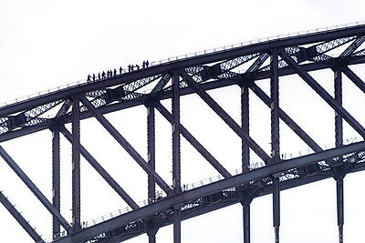 Silhouette people climbing Sydney Bridge against clear sky, Australia - p300m2144658 by Scott Masterton