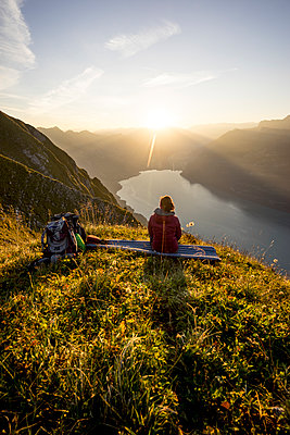 Female hiker sitting on viewpoint during sunset, Augstmatthorn, Switzerland - p300m2206851 by Matthias Aletsee