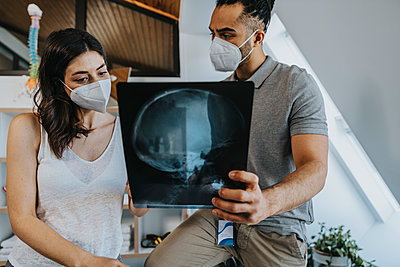 Male physiotherapist discussing x-ray image of neck and head with female patient in practice during pandemic - p300m2276821 by Mareen Fischinger