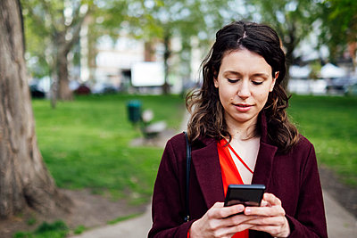 Young woman text messaging through mobile phone at park - p300m2298874 by ANTHONY PHOTOGRAPHY