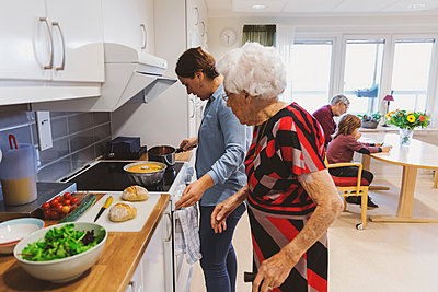 Side view of senior woman and daughter cooking food in kitchen - p426m1468265 by Maskot