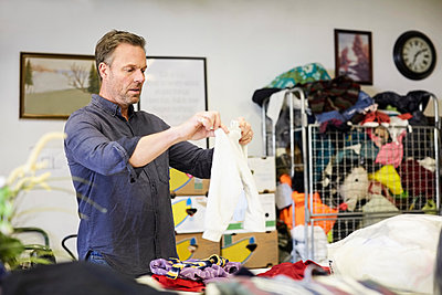 Mature male volunteer examining fabric at warehouse - p426m1542910 by Maskot