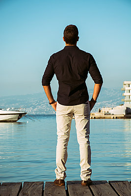 Rear view of a man standing on the wharf  - p794m1492958 by Mohamad Itani