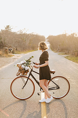 Young woman with bicycle looking sideways on rural road, Menemsha, Martha's Vineyard, Massachusetts, USA - p924m2058154 by Lena Mirisola